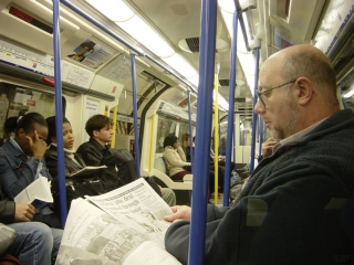 Guy reading newspaper in London